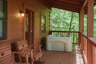 Cabin with a balcony and outdoor hot tub