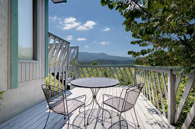 deck with table and chairs with mountain view